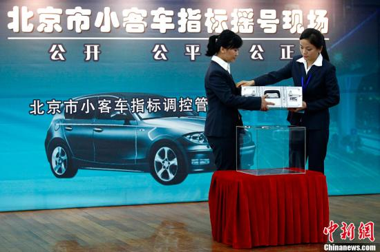 Two staff members announce results of vehicle plate lottery in Beijing. (File photo/China News Service)
