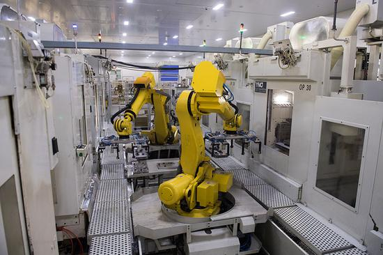 Industrial robots move production material in a factory of Wenzhou Ruiming Industrial Co Ltd in Ruian. (Photo/Xinhua)