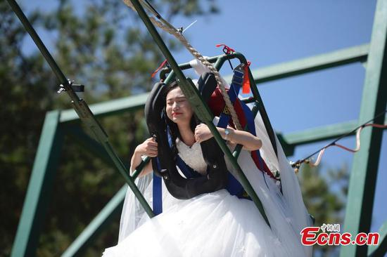 Woman takes unusual wedding dress photos on cliff swing