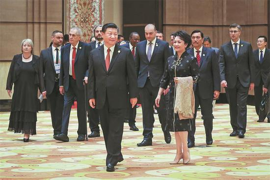 President Xi Jinping and his wife, Peng Liyuan, lead guests attending the China International Import Expo to a welcoming banquet in Shanghai on Sunday. (XU JINGXING / CHINA DAILY)