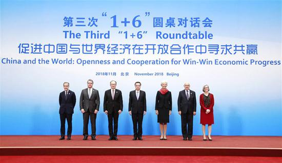 Chinese Premier Li Keqiang (C), together with World Bank Group President Jim Yong Kim (3rd L), IMF Managing Director Christine Lagarde (3rd R), WTO Director-General Roberto Azevedo (2nd L), OECD Secretary-General Angel Gurria (2nd R), Financial Stability Board (FSB) Chairman Mark Carney (1st L) and International Labor Organization (ILO) Deputy Director-General Deborah Greenfield (1st R), poses for a group photo before the third