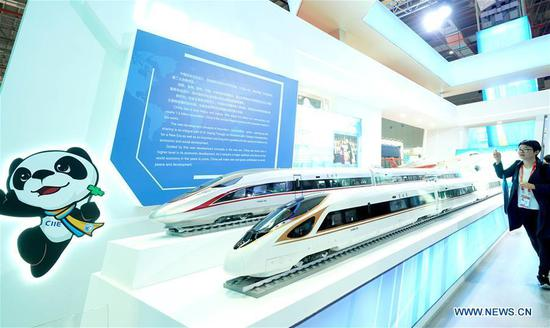 A journalist shoots models of China's Fuxing bullet train at the China Pavilion during the first China International Import Expo (CIIE) in Shanghai, east China, Nov. 5, 2018. (Xinhua/Chen Jianli)