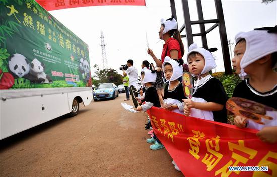 Children in giant panda costumes wait for the arrival of giant pandas