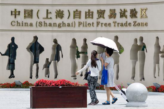 Pedestrians walk past the entrance of the China (Shanghai) Pilot Free Trade Zone. (Photo by Wu Jun/For China Daily)