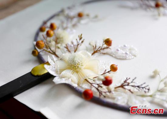 Girl makes embroidery works with dried flowers