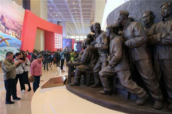 Visitors view a group statue commemorating the 40th anniversary of China's reform and opening-up at the National Museum of China in Beijing on Wednesday. (Wang Zhuangfei/China Daily)