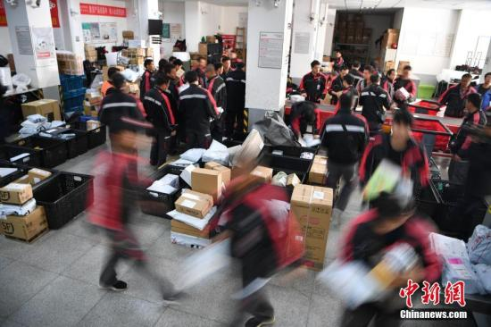 Logistics distribution workers sort packages. (File photo/China News Service)