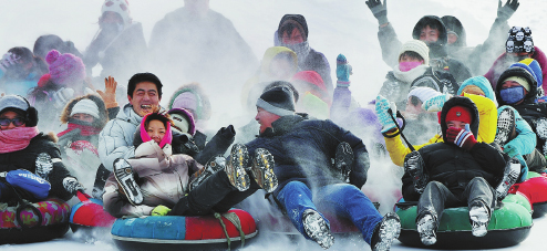 Visitors have a ball, sliding down a slope in Jilin. The province boasts high-quality snow and offers ideal temperatures for outdoor winter sports. (Photo by ZHOU SHI/FOR CHINA DAILY)
