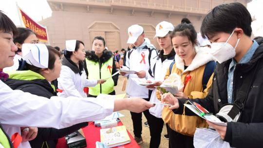 Medical workers and volunteers hand out brochures about HIV prevention to college students at the Daming Palace National Heritage Park in Xi'an, Shaanxi Province, on Saturday, World AIDS Day. (Photo by Yuan Jingzhi/China Daily)