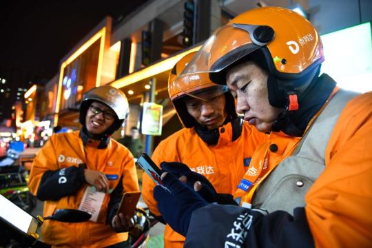 Food delivery employees check orders via mobile phones in Weifang, Shandong Province. (Photo/Xinhua)