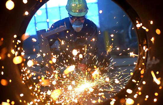 An employee performs welding operations at a private company in Zibo, Shandong province. (Photo/Xinhua)