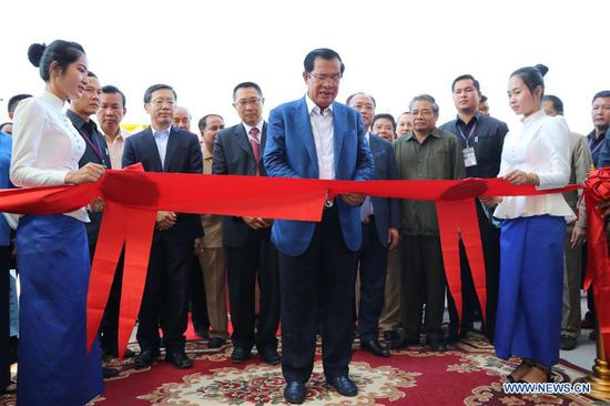 Cambodian Prime Minister Samdech Techo Hun Sen cuts the ribbon during an inauguration of the Lower Sesan II hydroelectric power station in Stung Treng province, Cambodia, Dec. 17, 2018. The Chinese-built Lower Sesan II hydroelectric power station was inaugurated here in far northeastern Cambodia on Monday after almost five years of construction. (Xinhua/Mao Pengfei)