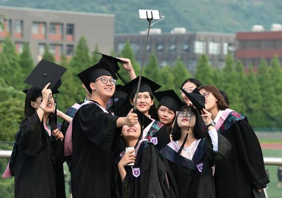 Nanjing University students take group photos after their graduation ceremony. [Photo/Xinhua]