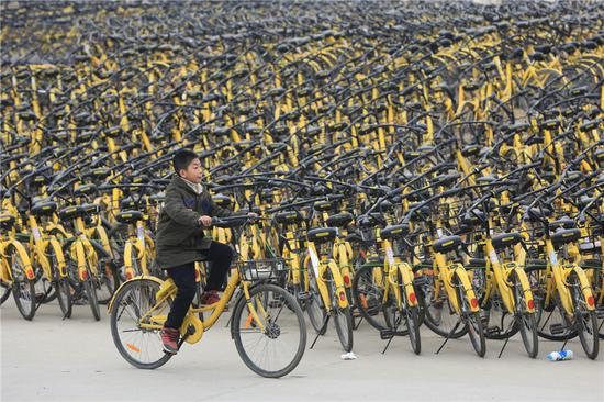 An Ofo customer rides past piles of the company's bikes in Xiangyang, Hubei province. (Photo by Guo Qi/For China Daily)