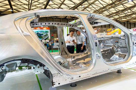 Visitors check out a Novelis aluminum flat-rolled product during an automobile expo in Shanghai. (Photo provided to China Daily)