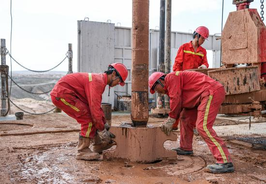 Employees of a petroleum exploration company work at a newly established drilling platform in Aksu, the Xinjiang Uygur autonomous region. (Photo/Xinhua)