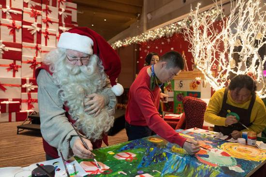 A certified Santa Claus from Finland makes his rounds at a Hyatt hotel in Shanghai bringing the festive cheer to guests. (Photo/chinadaily.com.cn)