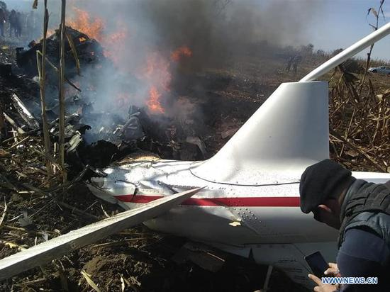Photo taken with a mobile device shows a man taking images of the debris of the helicopter in Coronango, Puebla, Mexico, Dec. 24, 2018. Governor of Mexico's central state of Puebla Martha Erika Alonso and her husband Rafael Moreno Valle, ex-governor of the state, were killed in a helicopter crash on Monday, head of the National Action Party Marko Cortes said. (Xinhua/Antonio Rivas)