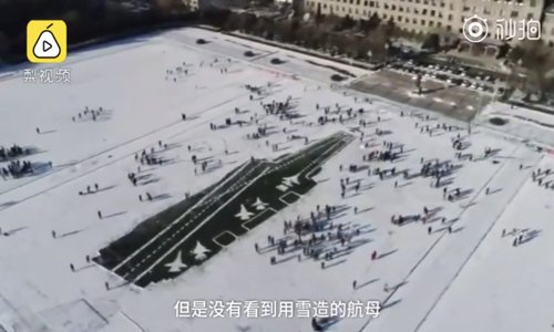 Students use shovels and their feet to tamp down snow and they also created five aircraft on the carrier's deck. (Screenshot photo)