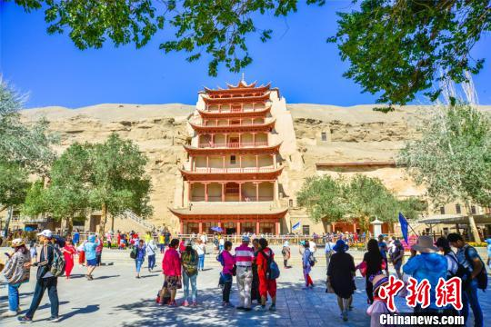 Tourists visit Mogao Grottoes in Dunhuang City, Northwest China's Gansu Province, in July 2018.  (Photo/China News Service)