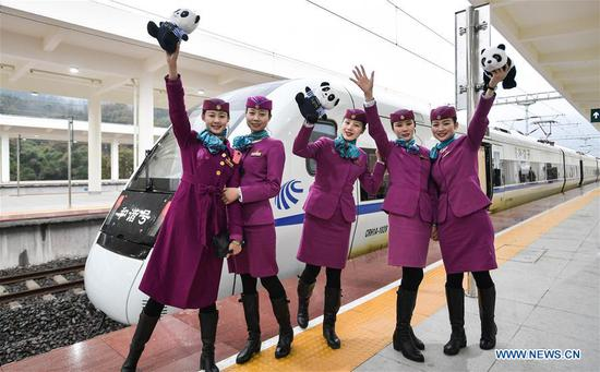 The train conductors pose for photos before the bullet train of Chengdu-Ya'an high-speed railway at Ya'an station in Ya'an, Southwest China's Sichuan province, on Dec 28, 2018. (Photo/Xinhua)