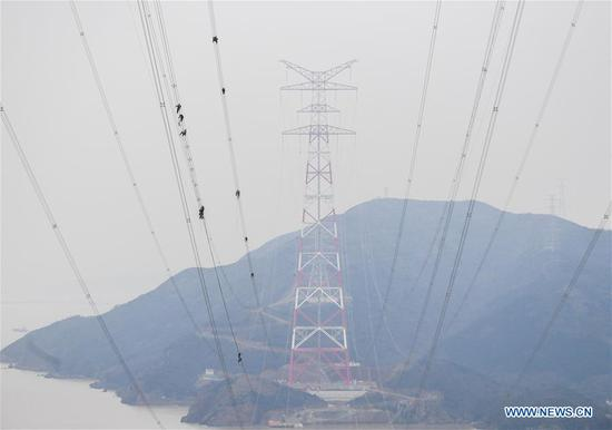 World's highest power supply pylons complete cable construction in Zhoushan, E China's Zhejiang