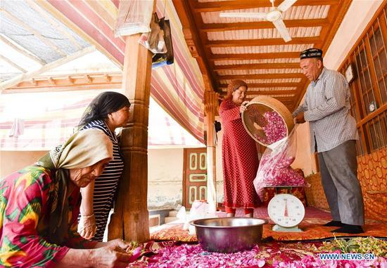 Flower grower Ruz and his wife Tajinisa weigh rose petals used for making rose sauce at a village in Hotan, northwest China's Xinjiang Uygur Autonomous Region, June 6, 2018. (Xinhua Photo)