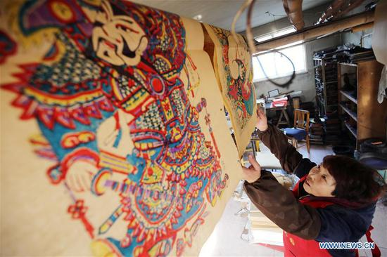 Folk artists make woodblock New Year paintings for Spring Festival