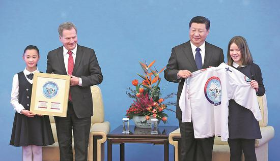President Xi Jinping and Finnish President Sauli Niinisto, attending the inauguration of the 2019 China-Finland Year of Winter Sports, are given items with the year's logo by children from each country at the Great Hall of the People in Beijing on Monday. (Photo by Feng Yongbin/China Daily)