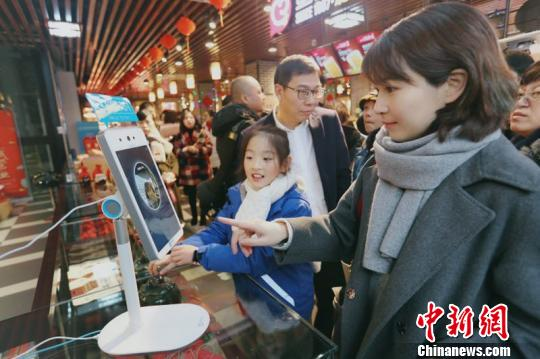 A consumer tries facial recognition payment in a shop on the Five-horse Street in Wenzhou City, Zhejiang Province. (Photo provided to China News Service)