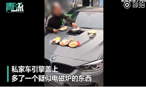 A man cooks hot pot on a car hood. (Screenshot photo)