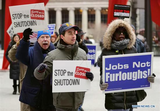 People hold placards during a rally to protest against the partial government shutdown at Federal Plaza in Chicago, the United States, on Jan. 18, 2019. Dozens of federal employees and activists gathered here on Friday to protest against the ongoing partial government shutdown, which is now the longest in U.S. history. (Xinhua/Wang Ping)