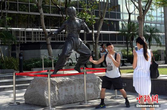 A visitor poses in front of the Bruce Lee statue  of the Avenue of Stars in Hong Kong, Nov. 17, 2015. (File photo/China News Service)