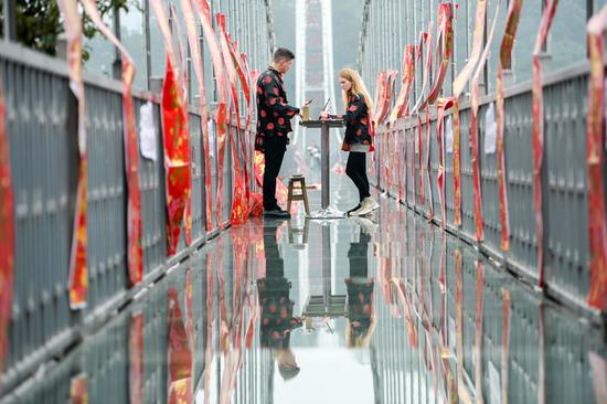 Foreign tourists show off calligraphy skills on glass bridge