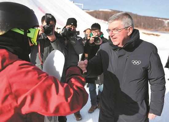 Thomas Bach, president of the International Olympic Committee, bumps fists with a skier while visiting a venue of Beijing's 2022 Olympic Winter Games on Tuesday in Zhangjiakou, Hebei province. [Photo/Xinhua]