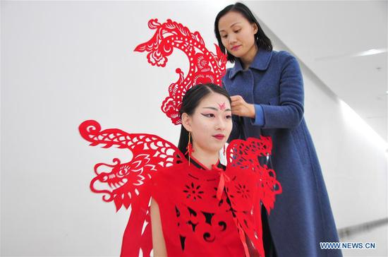 Craftswoman makes papercutting works of cheongsam to greet Spring Festival