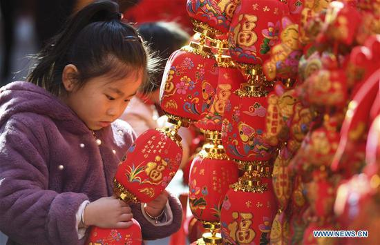 A child looks at Spring Festival decoration at a market in Hefei, capital of east China's Anhui Province, Jan. 26, 2019. Red decorations are arranged across China to greet the upcoming lunar New Year which will fall on Feb. 5 this year. (Xinhua/Liu Qinli)