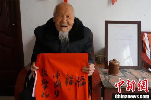 Zhang Xueli, a 117-year-old in Jiaxian county, Henan province, shows the Chinese calligraphy he has written. (Photo/Chinanews.com)