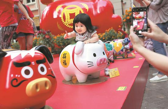 A child's fascination with the zodiac sign for the new lunar year is captured in a photograph in Hong Kong on Thursday. Performers put on lion dances and set off fireworks in San Francisco on Tuesday to celebrate Chinese New Year. (Photo/Xinhua)