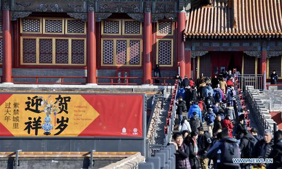 Tourists walk past a poster celebrating the Spring Festival in the Palace Museum, also known as the Forbidden City, in Beijing。(Xinhua/Li Xin)