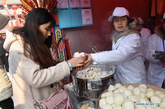 A tourist buys snacks at a temple fair of the Badachu Park in Beijing, capital of China, Feb. 5, 2019, the first day of Chinese Lunar New Year. (Xinhua/Li Jundong)