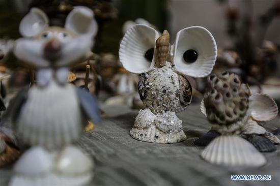 Palestinian young man makes artistic forms out of seashells