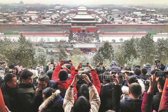 Visitors photograph the snowy scene at the Forbidden City from Jingshan Park in Beijing on Tuesday. [Photo by Du Lianyi/China Daily]