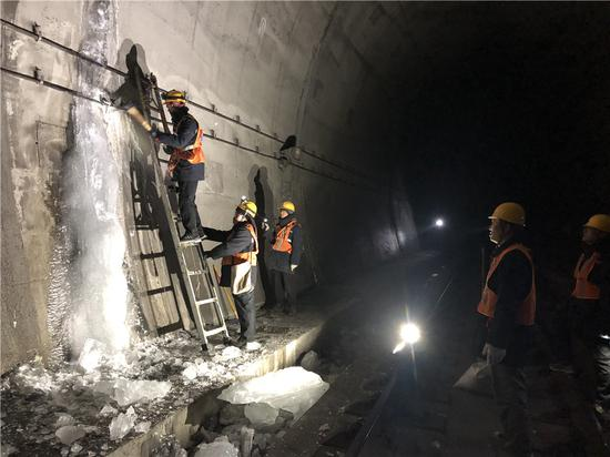 Members of the maintenance squad clear ice on the wall of a tunnel along the Lyuliang section of the Taiyuan-Zhongwei-Yinchuan railway in Shanxi province. (SUN RUISHENG/CHINA DAILY)