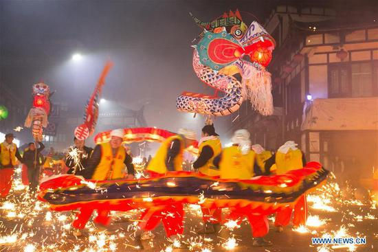 People perform dragon dance to celebrate upcoming Lantern Festival