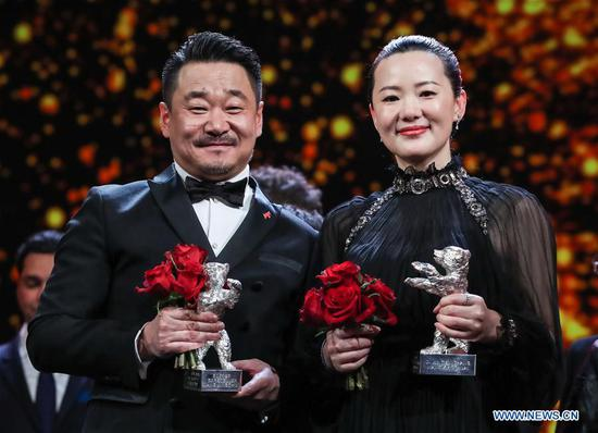 Chinese actor Wang Jingchun (L) and actress Yong Mei pose for photos after the award ceremony of the 69th Berlin International Film Festival in Berlin, capital of Germany, Feb. 16, 2019. Chinese actor Wang Jingchun and actress Yong Mei won the Silver Bears for Best Actor and Best Actress for their performances in the film