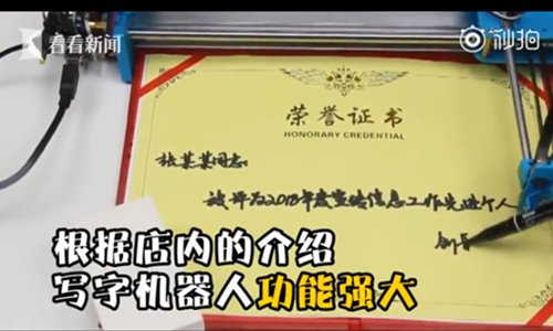 A handwriting robot is writing on a piece of honorary certification. (Screenshot photo/Kankan News)