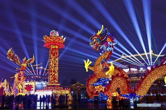 Visitors view lanterns at a scenic spot in Xi'an, capital of northwest China's Shaanxi Province, Feb. 17, 2019. Many places across the country are decorated with lanterns to celebrate the upcoming Lantern Festival, which falls on Feb. 19 this year. (Xinhua/Jiao Hongtao)