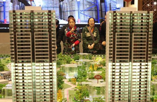 Investors look at a model of a residential project in Chongqing. (Photo by Sun Kaifang/For China Daily)
