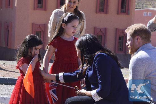 2019年2月24日,英国哈里王子和妻子梅根在访问摩洛哥阿斯尼的女子寄宿学校期间与两名少女交谈。(新华社照片)